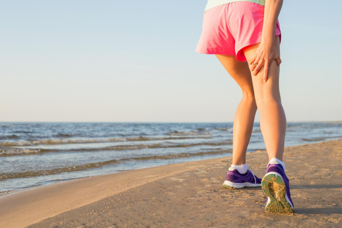 Person with hamstring tendonitis holding back of thigh in pain while running on beach