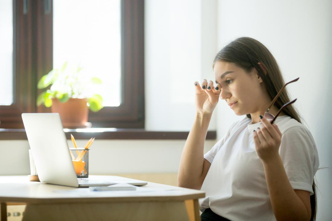 woman with a headache and fatigue at her desk