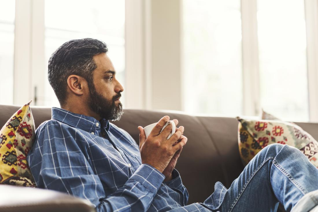 man sitting on settee drinking coffee
