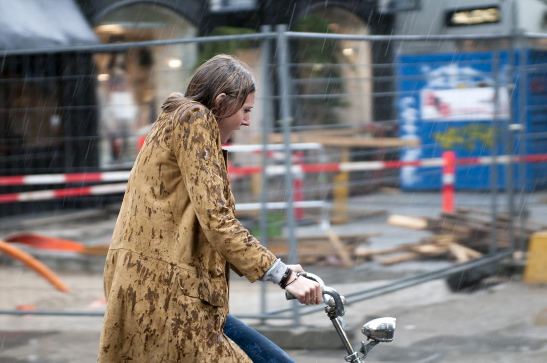 Woman riding her bike in the rain who may have chills without fever