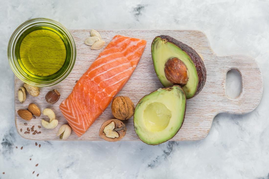 salmon, nuts and avocado on a board which are part of low carb diet for diabetics