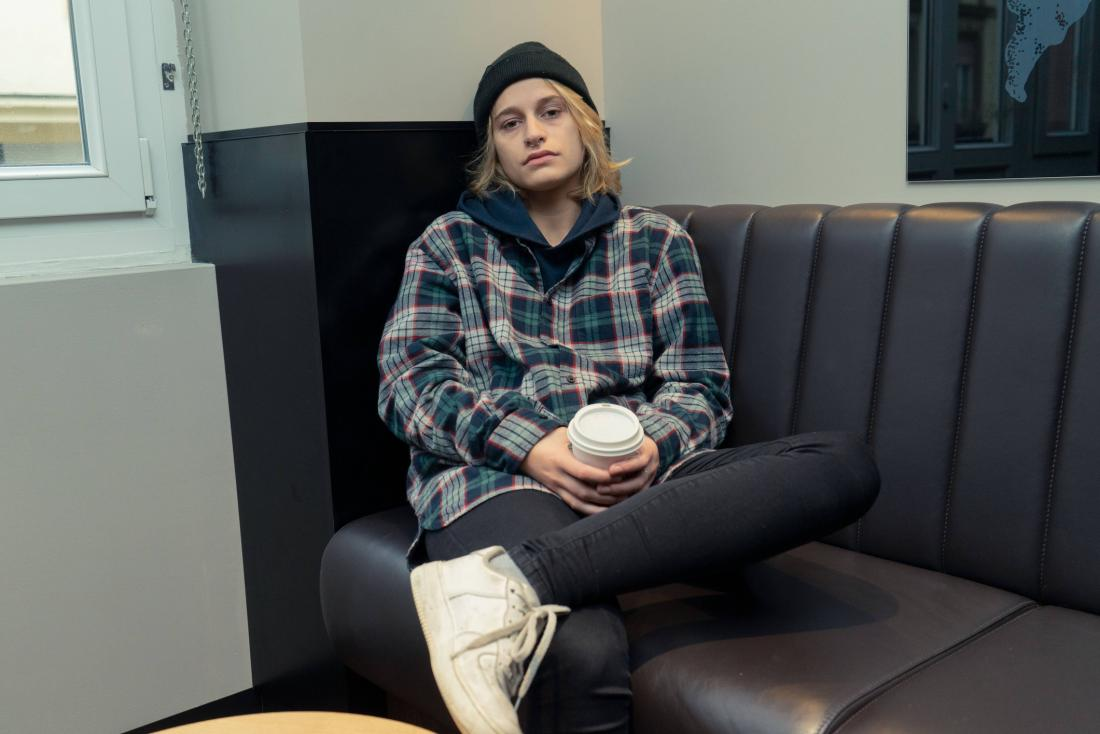stressed person sitting on the sofa holding a drink