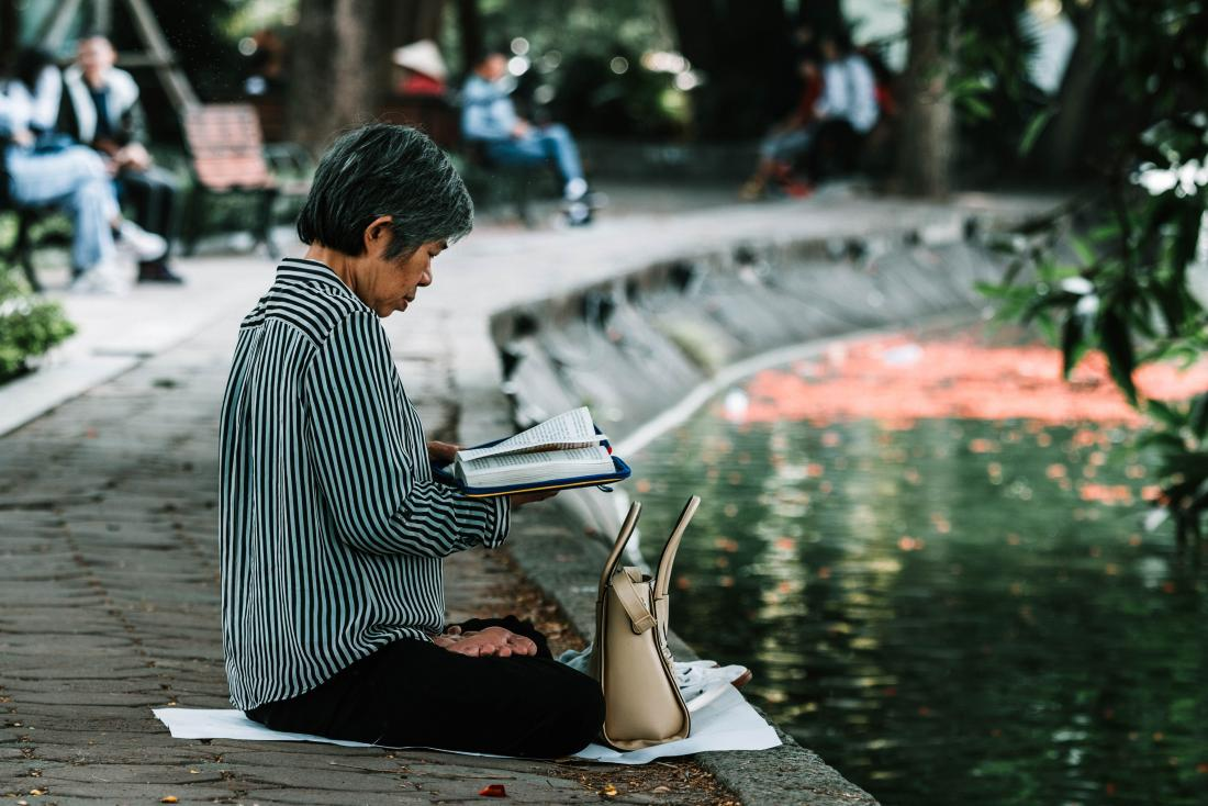 older person sitting cross legged reading a book