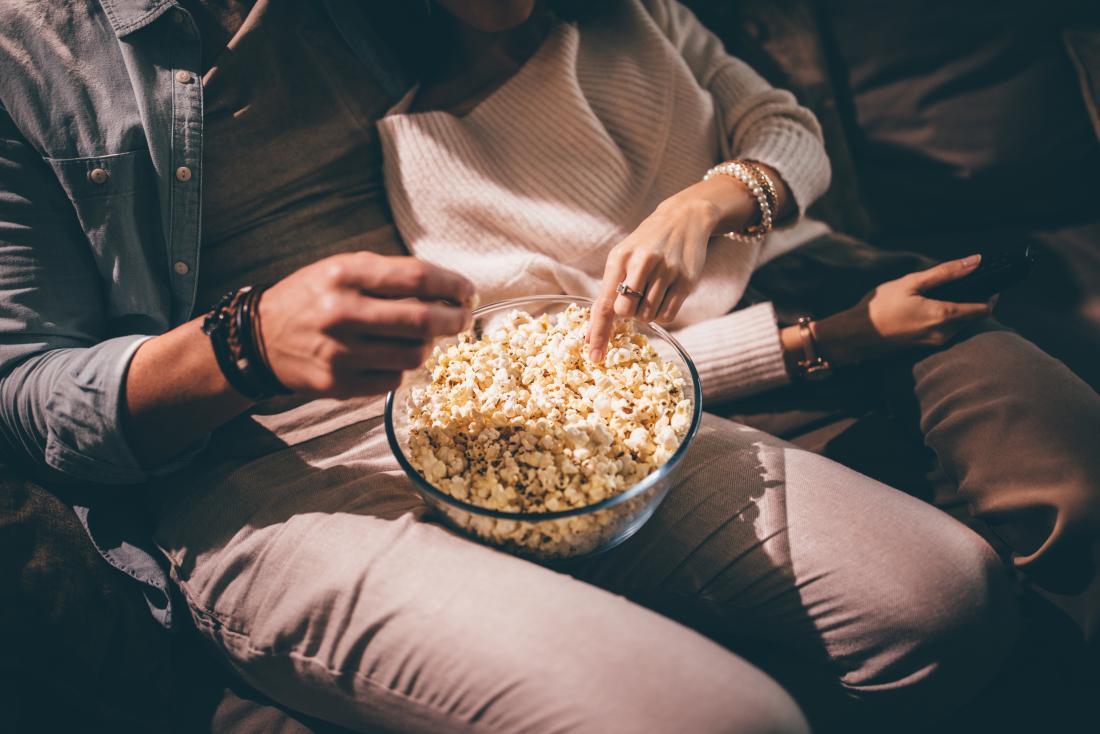 Couple snacking on popcorn