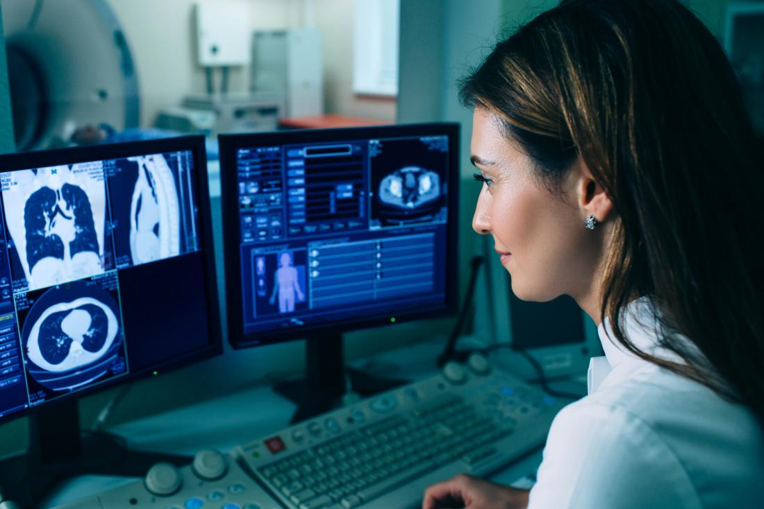 doctor looking at lung scans on computer screen
