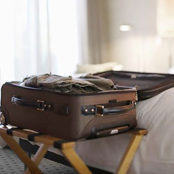 An open suitcase in a hotel room.