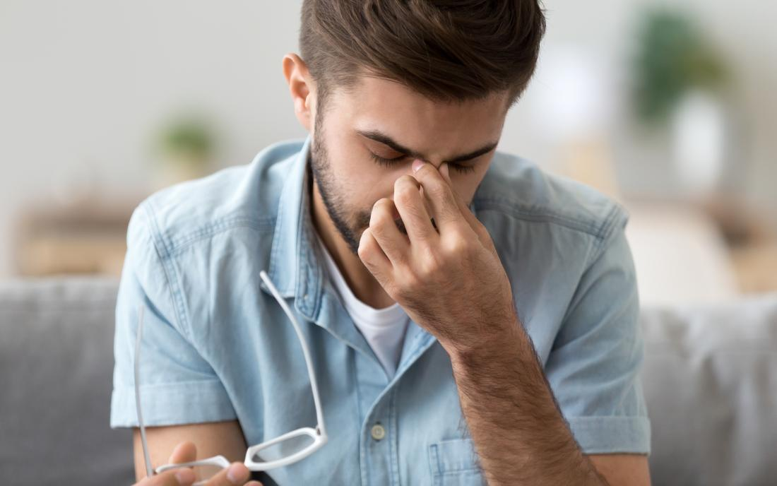 Man with headache or eye strain holding bridge of nose because of sinus pain
