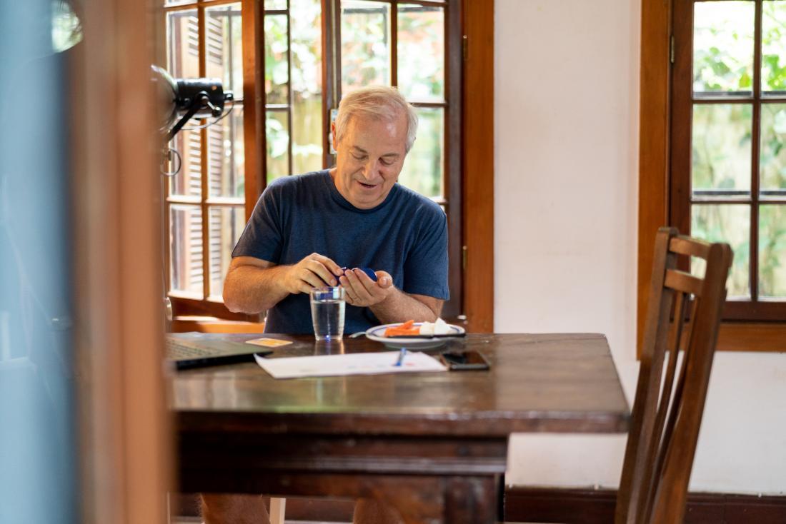 senior man taking medication while eating lunch