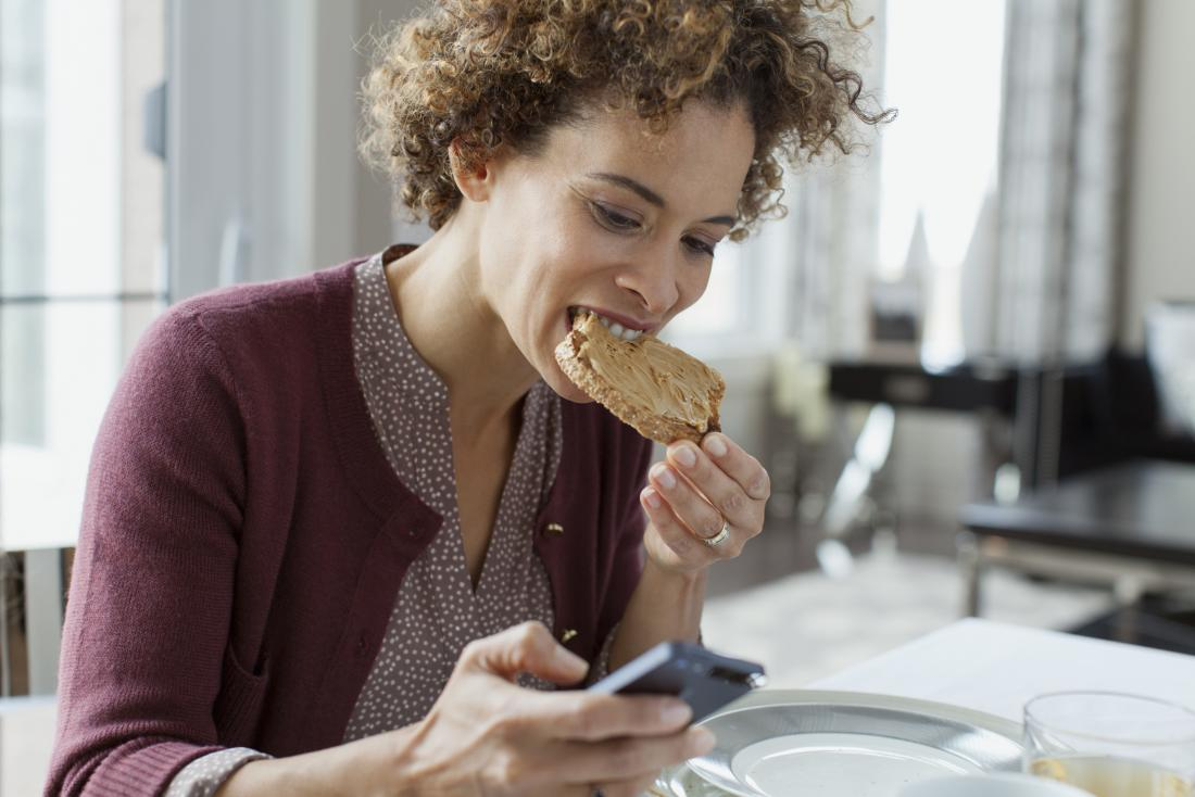 woman eating toast while looking at mobile phone