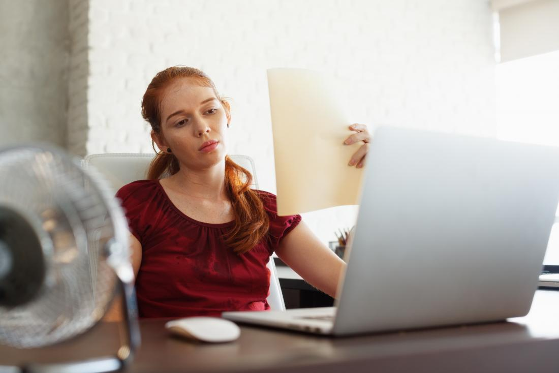 Woman sitting at desk at work sweating with heat intolerance using fan to cool down.