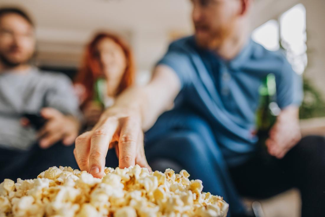 man reaching for popcorn