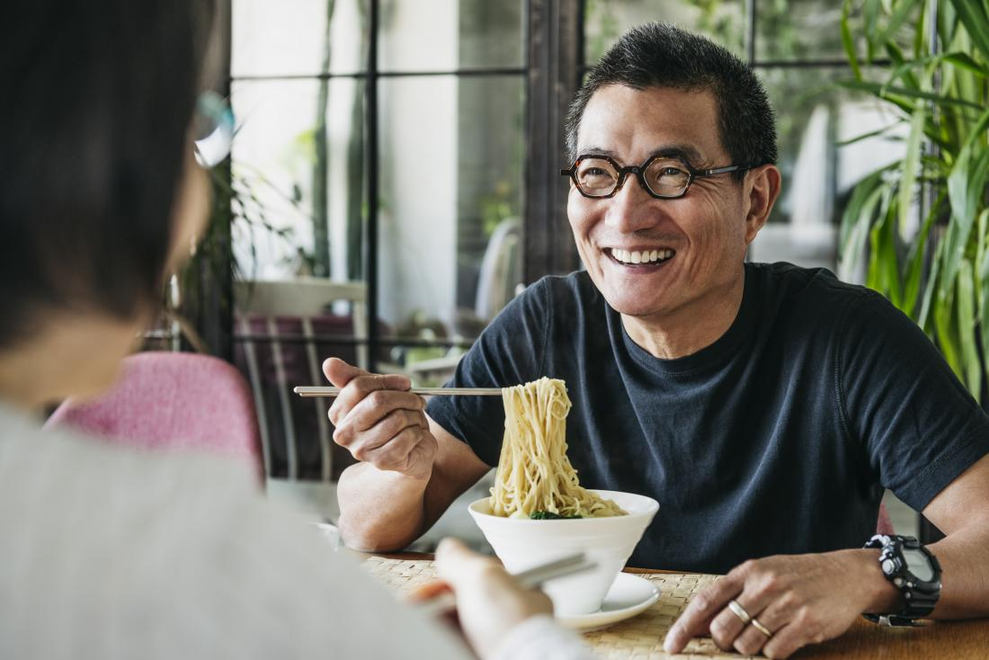 Man eating noodles in restaurant smiling and happy preventing type 2 diabetes