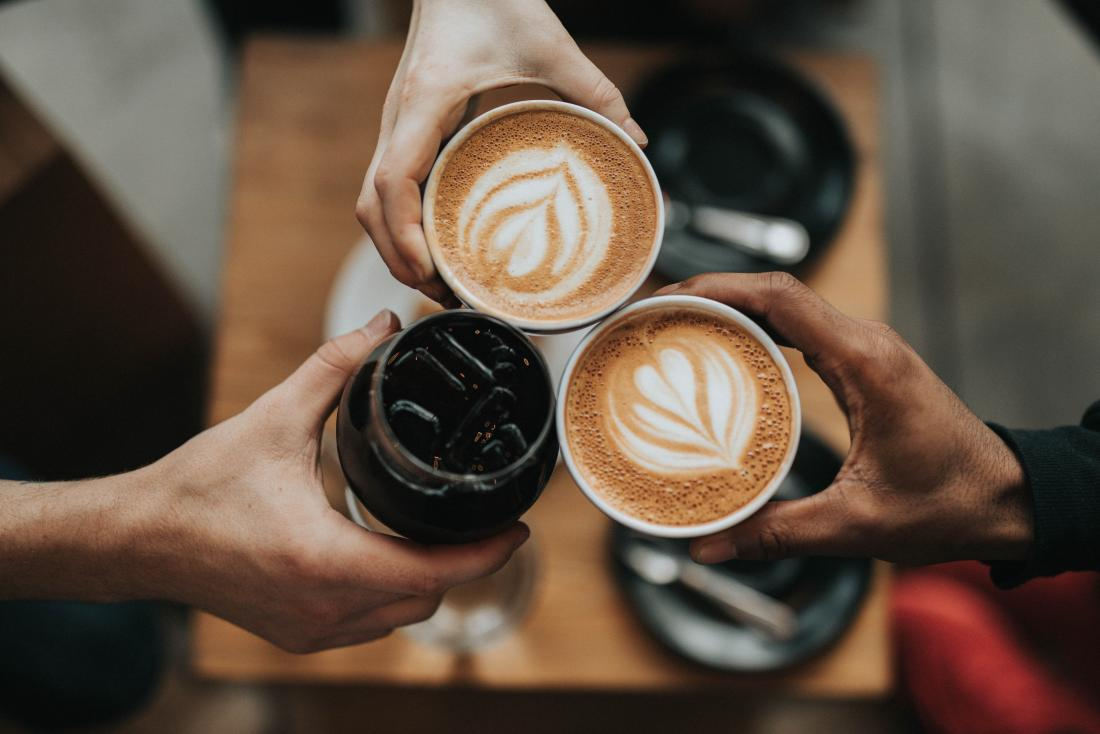 three hands golding cups of coffee