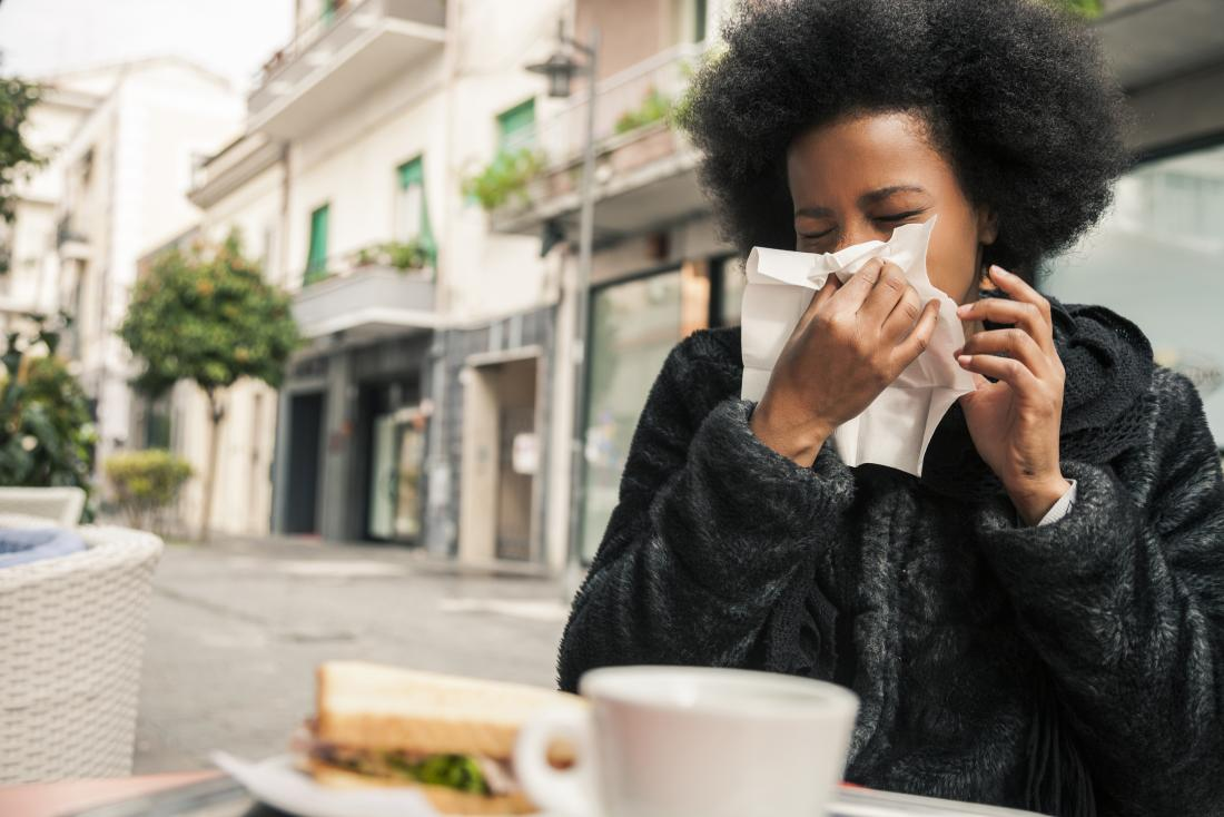 woman sitting at outdoor cafe blowing nose into tissue