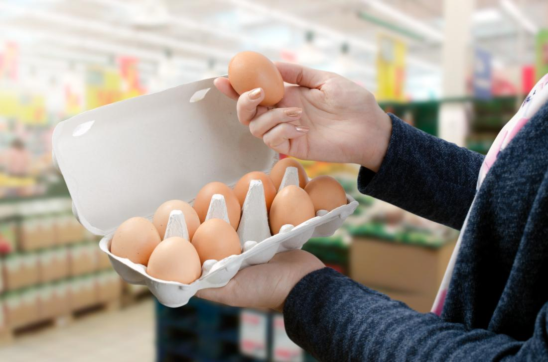 Woman holding an egg in a supermarket