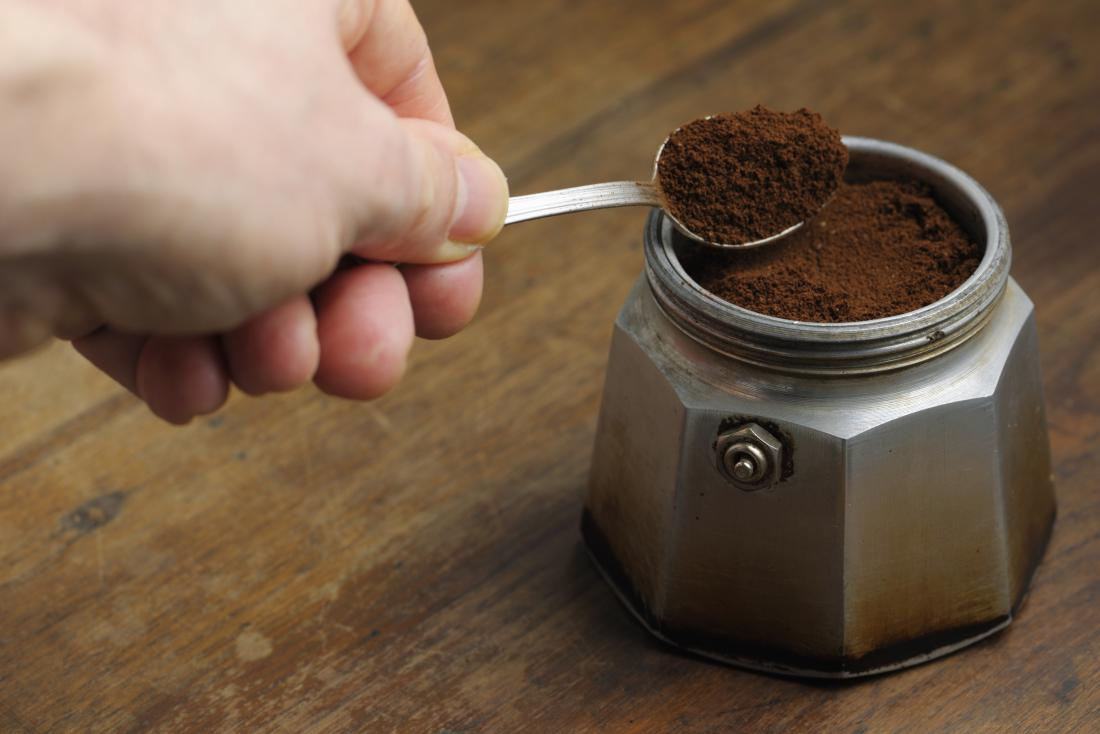 person spooning coffee grounds