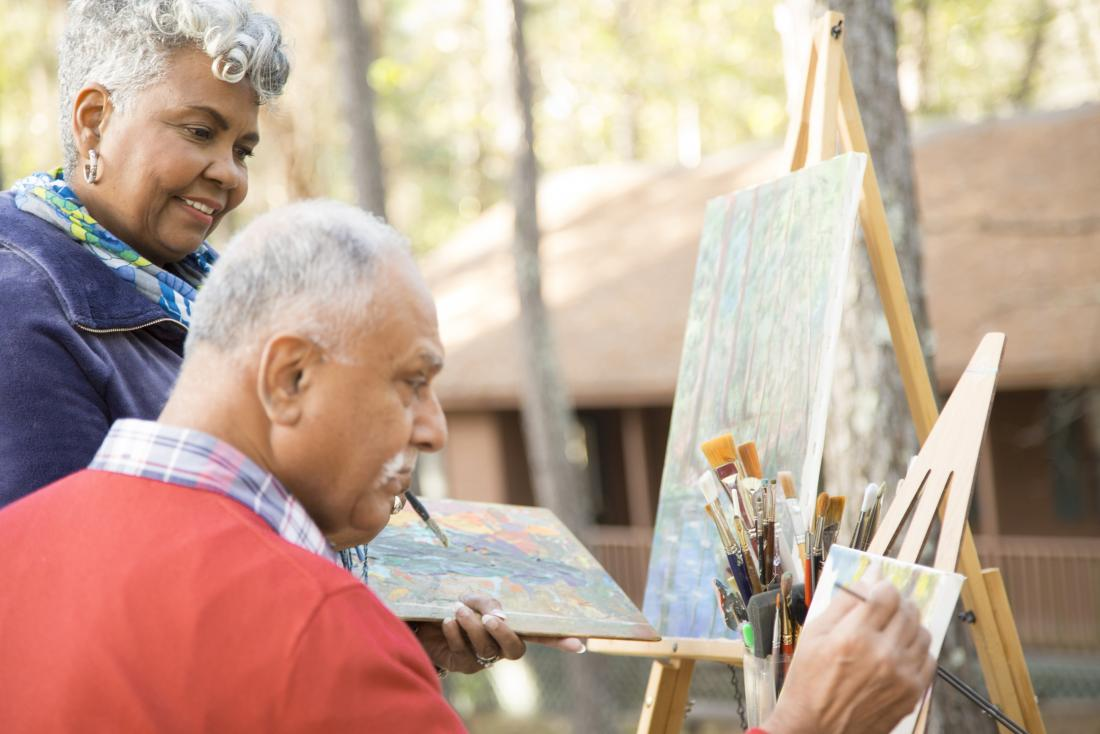 Senior mature adults doing painting and art therapy outdoors