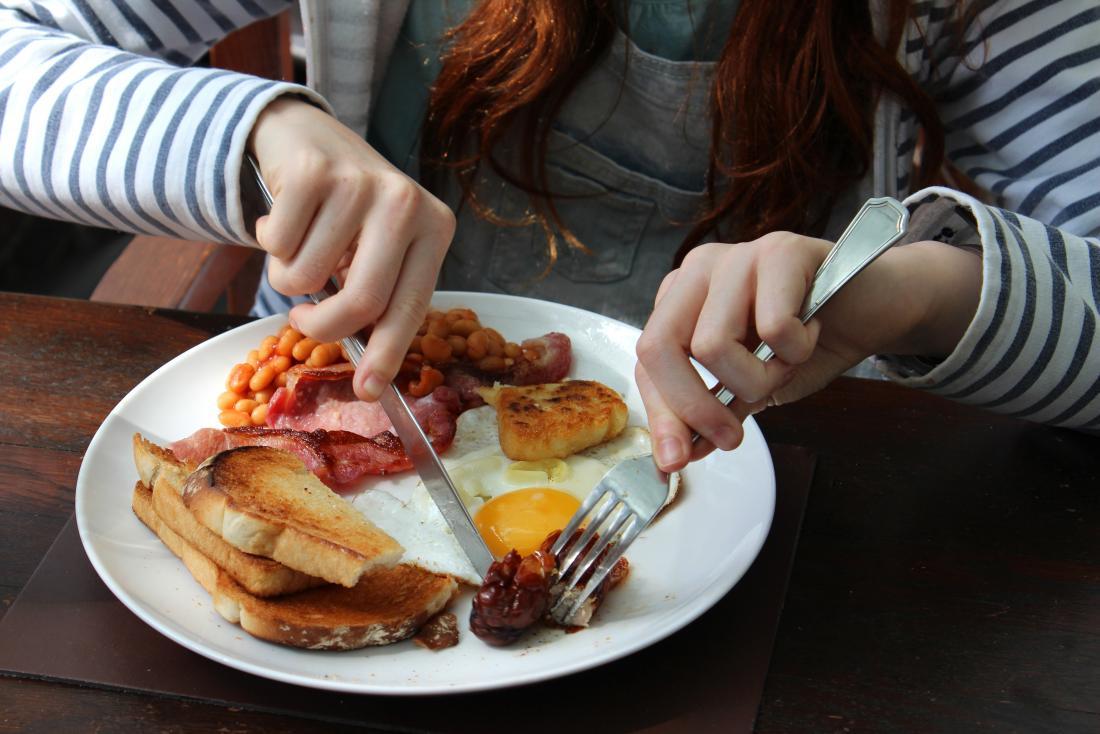girl eating fried breakfast