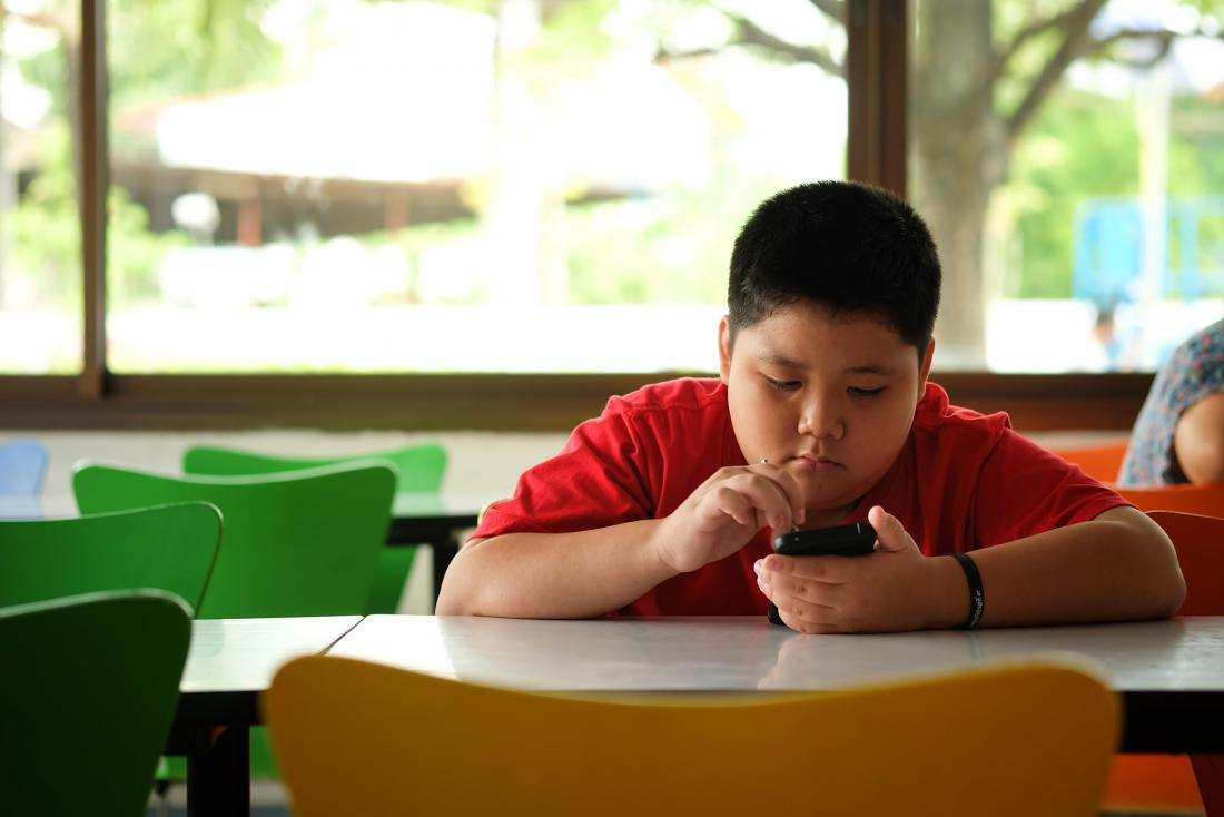young boy with obesity looking sad sitting at a table