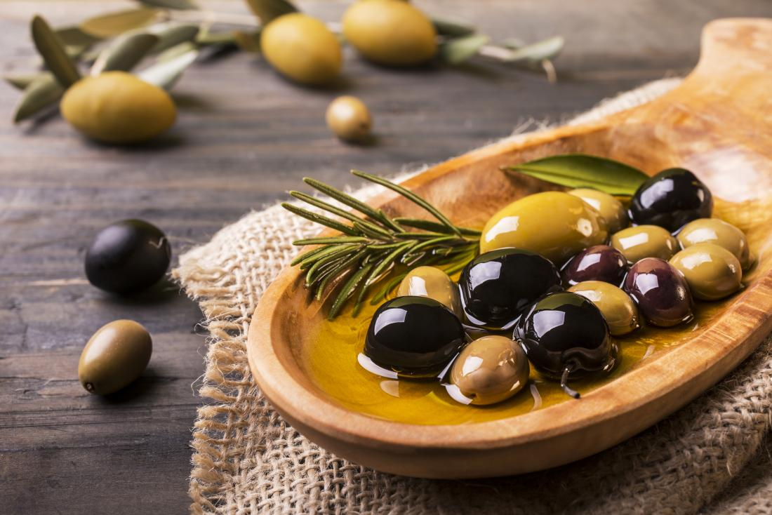 Different types of olives in oil in wooden bowl