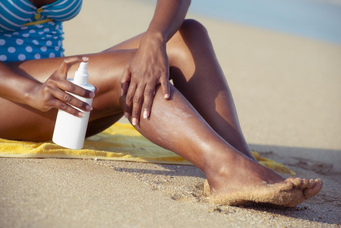 Person with black or brown skin sitting on beach applying sunscreen
