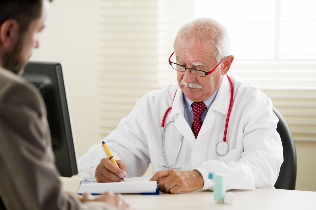 doctor and male patient with inhaler on table