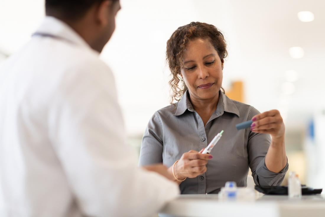 patient taking blood sugar test with doctor