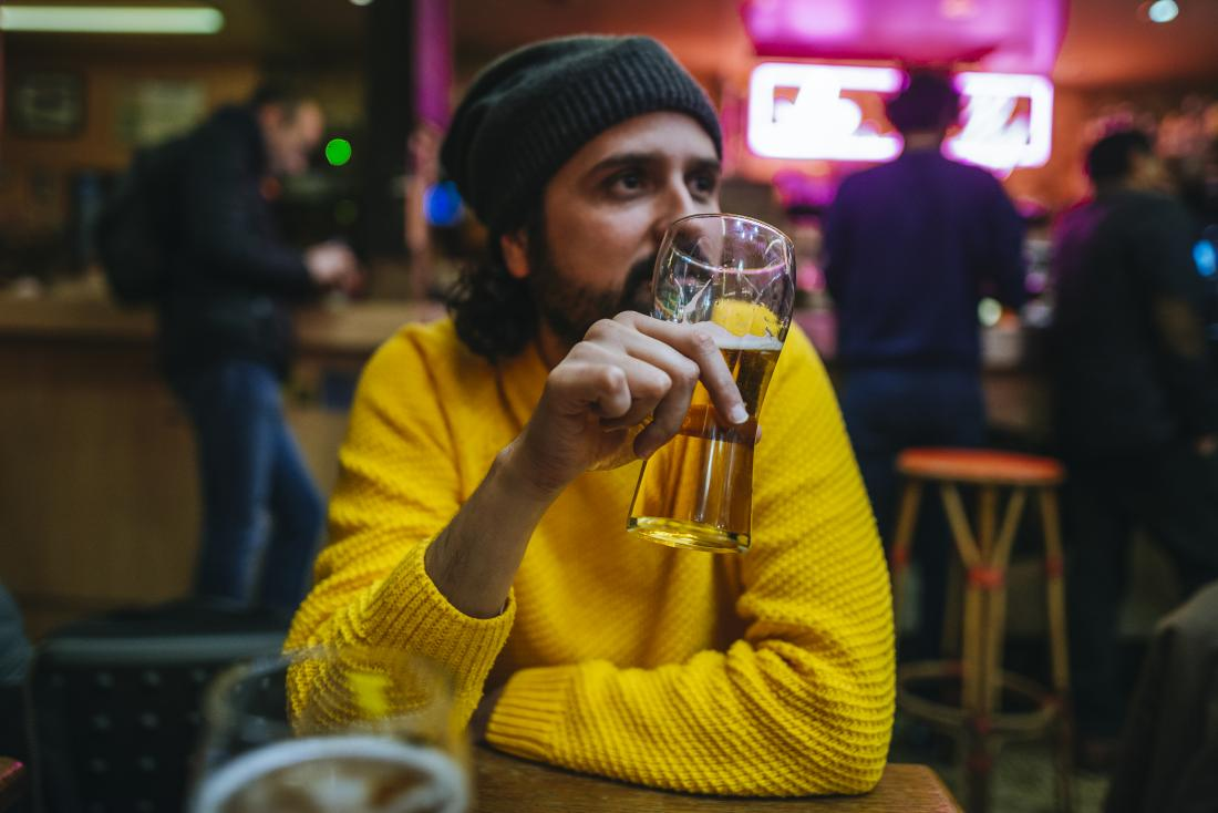 Man drinking beer or alcohol in bar