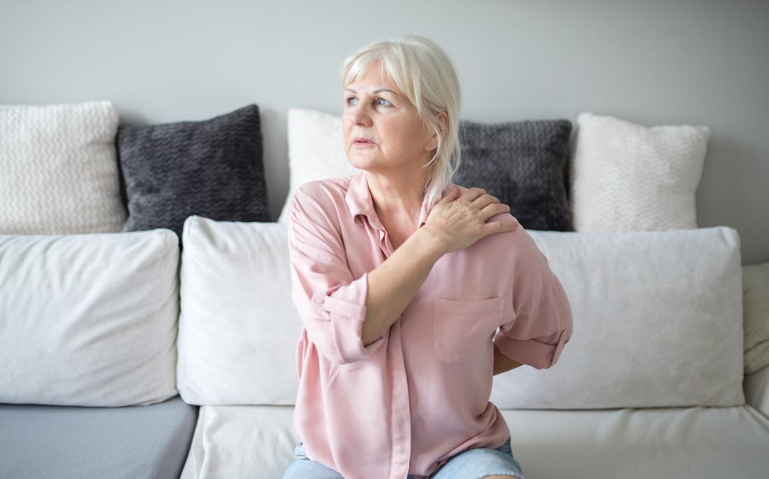 senior woman sitting on settee holding her shoulder in pain
