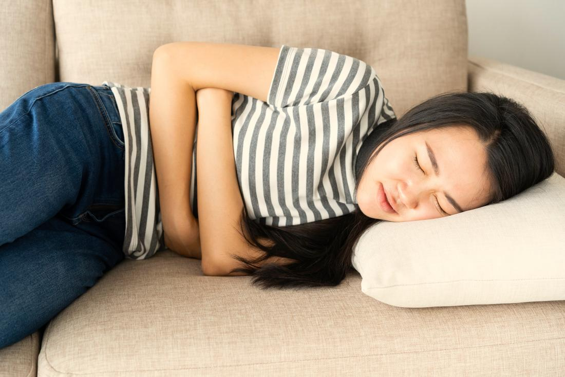 Woman on a sofa holding her stomach due to stomach pain and nausea