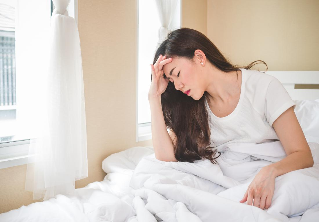 Woman sitting up in bed who has dizziness when lying down