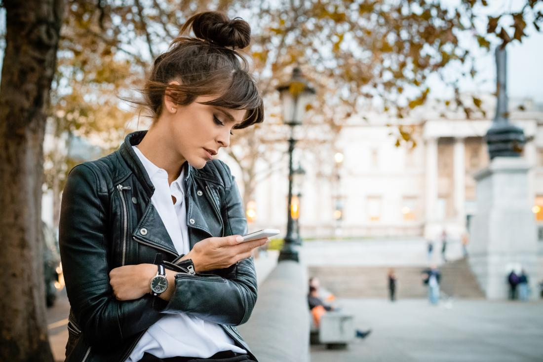 Woman on her phone worrying about spotting before period
