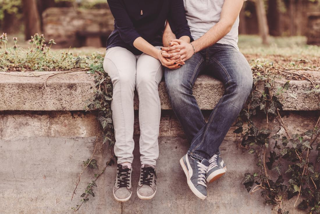 couple sitting on wall and holding hands