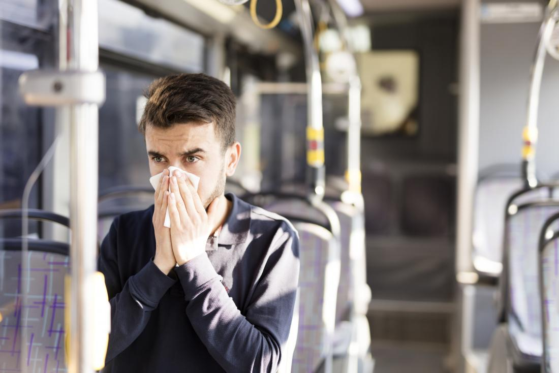 Man with sinusitis blowing nose with tissue on bus