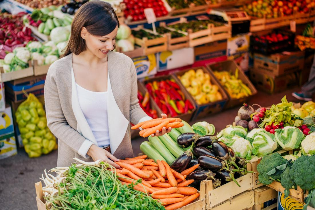Woman shopping for fresh vegetables for a low protein diet