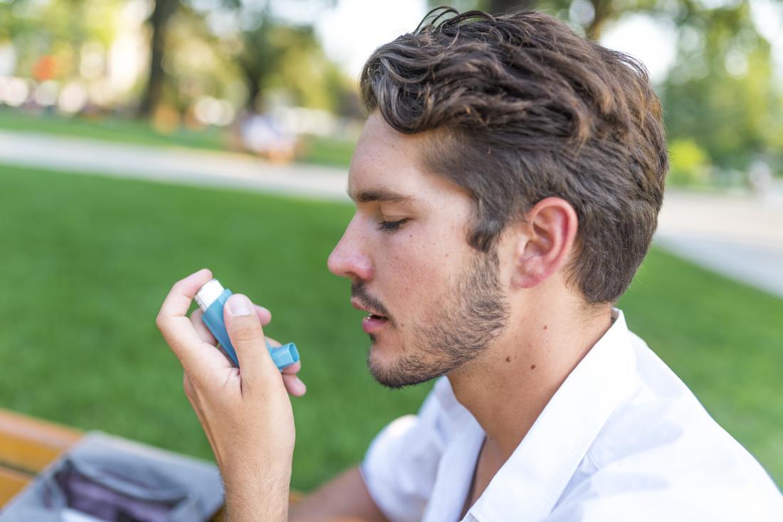 Man with asthma using inhaler.