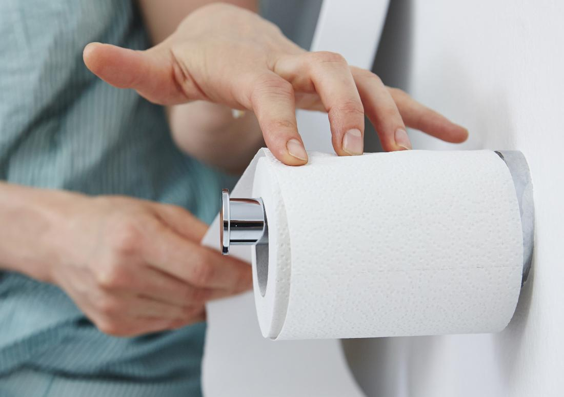 Woman experiencing blood in urine pulling toilet roll