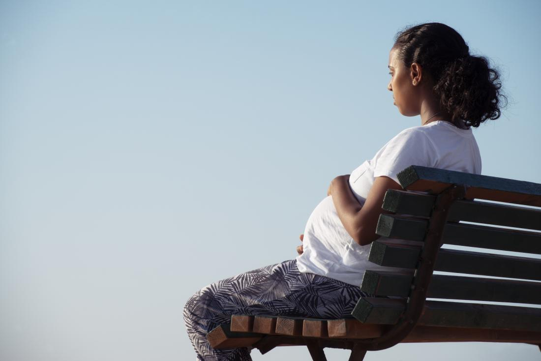 pregnant woman sitting on a bench