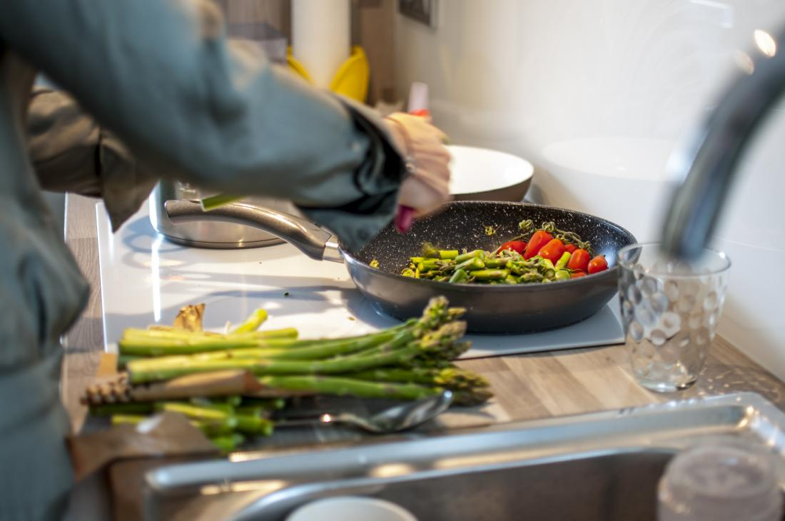 man cooking with asparagus