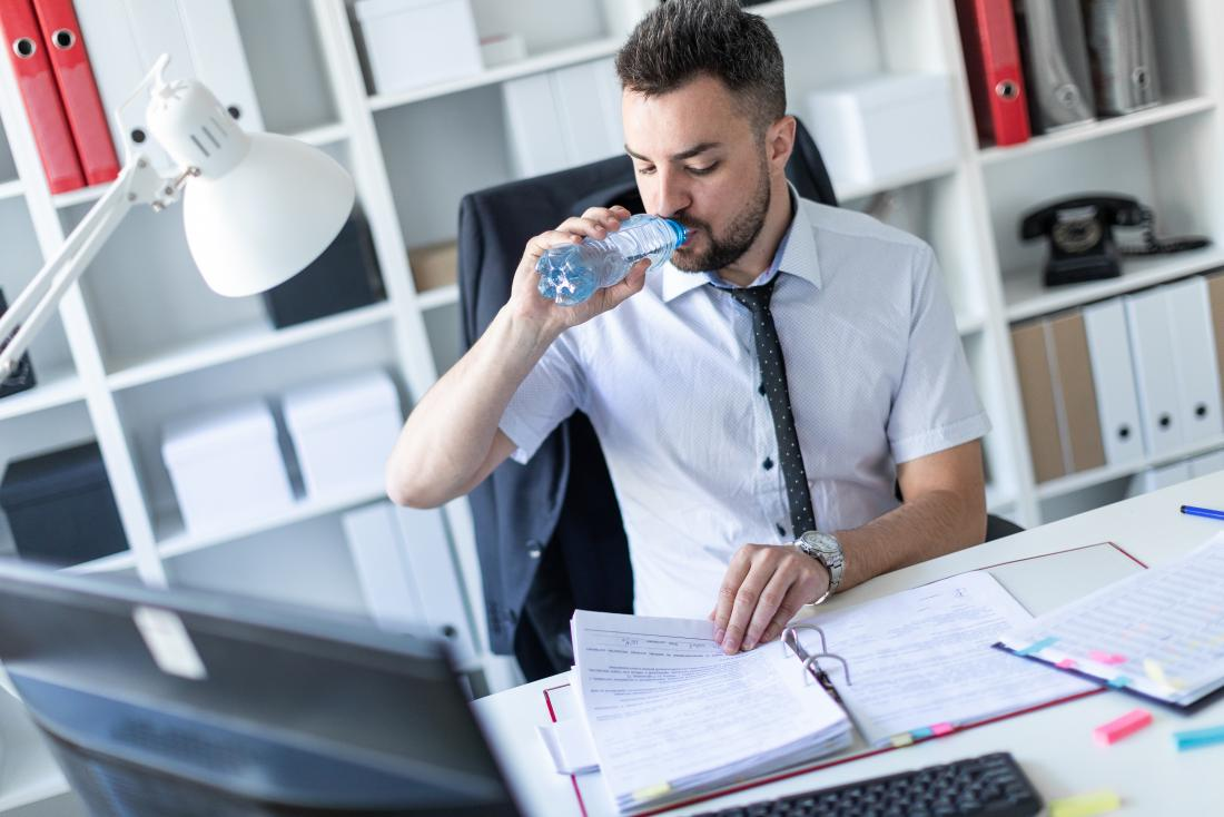 young man at work desk drinking bottle of water