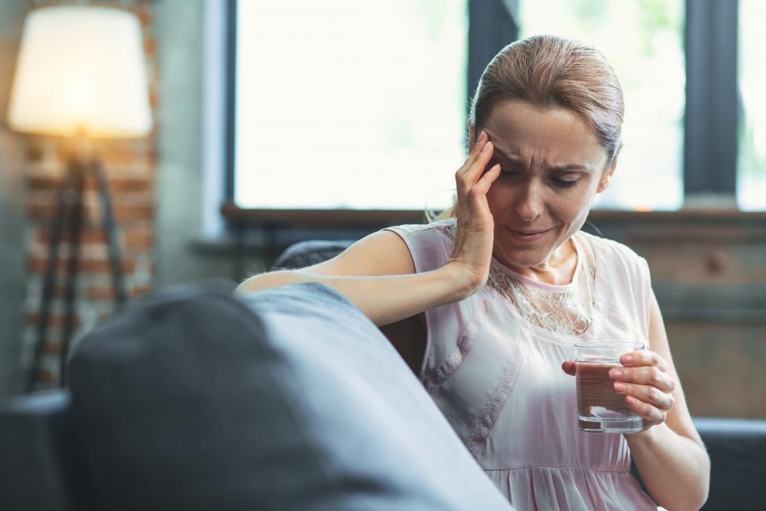 Woman experiencing headache and neuralgia in face holding glass of water in pain