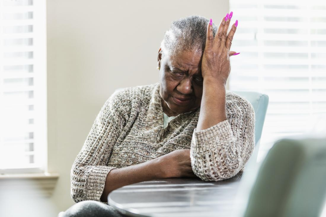 senior lady holding head in pain