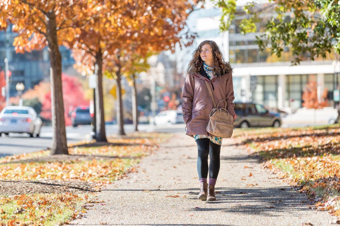Woman walking through city park in winter coat.