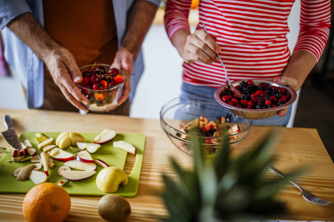 People making a fruit salad in kitchen using berries and apples for whole30 diet