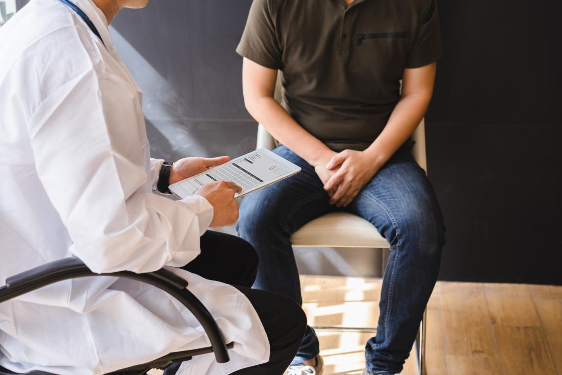Man with urethral syndrome sitting with hands covering crotch in doctor's office