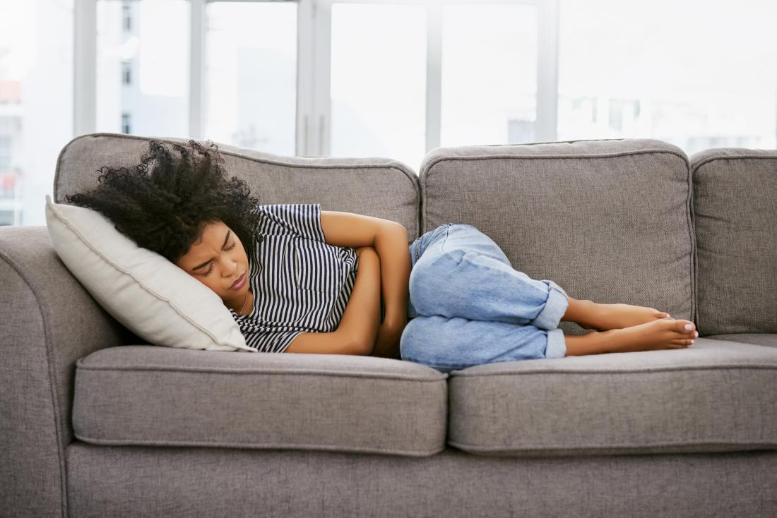 Woman on the sofa holding her stomach due to severe stomach pain