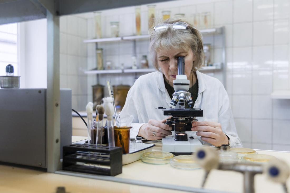 researcher examining something through the microscope