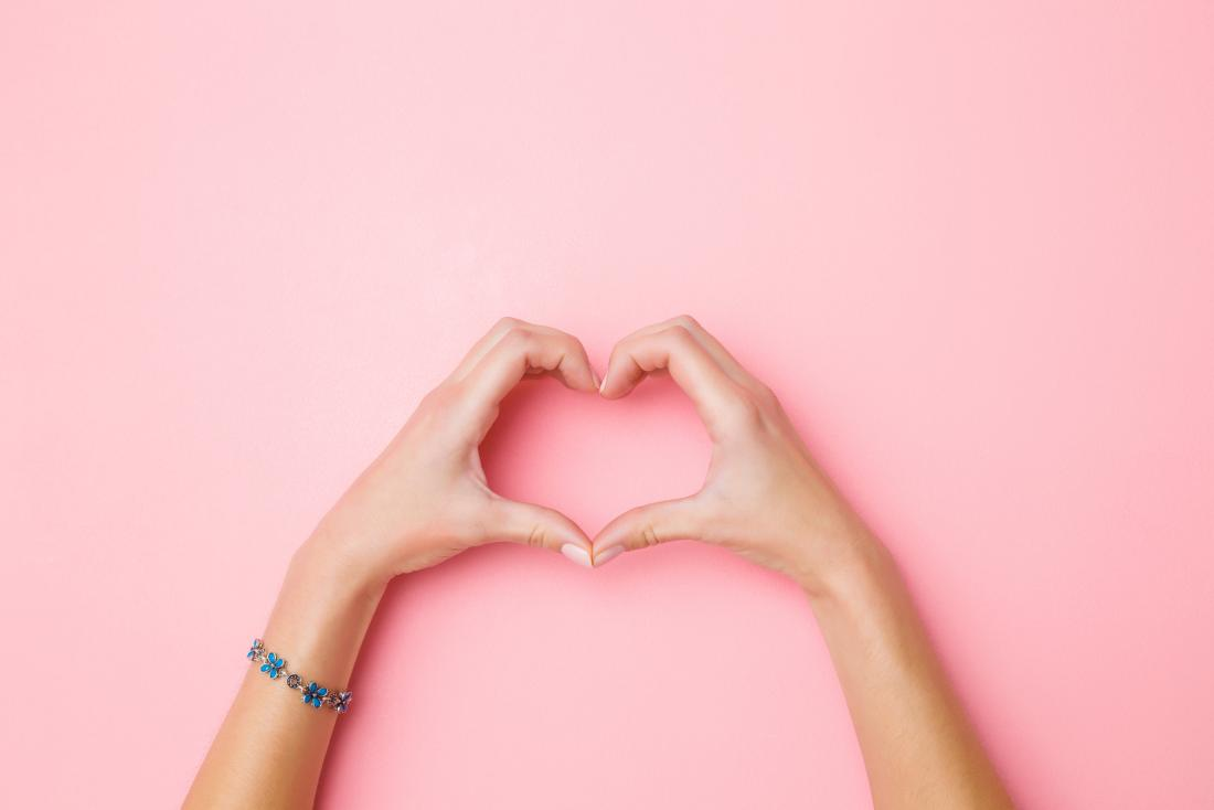 woman's hands forming a heart symbol against pink background