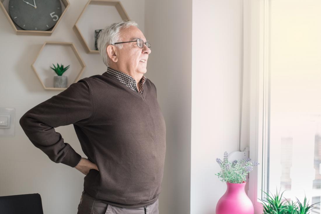 Senior man with lower back pain while standing or walking.