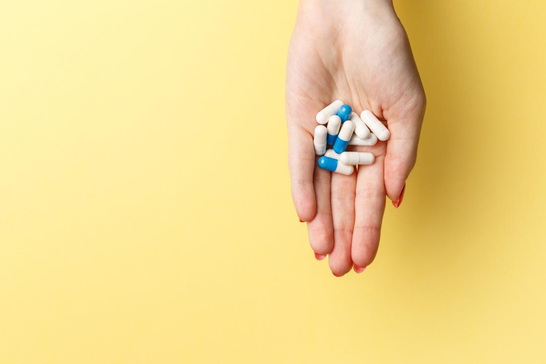 woman's palm holding white and blue pills against yellow background